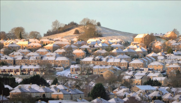 A photograph of a cluster of snow-topped houses
